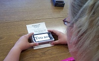 A teenage girl uses a screen magnifier on her phone.