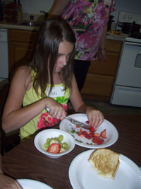 A girl cuts strawberries with a knife.