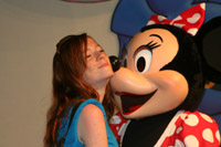 Minnie Mouse kisses a girl on the cheek