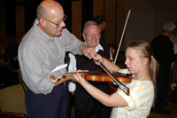 A violinist from the symphony looks on as a young girl tries to play his violin