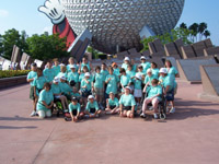 A group of about 50 children and volunteers stand in front of Spaceship Earth at Disney's Epcot theme park