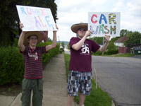 Two teenage boys hold ups signs that say rummage sale and car wash