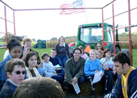 A group sits on bales of hay in the hay ride wagon
