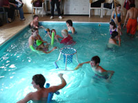 A group of children swim in an indoor pool