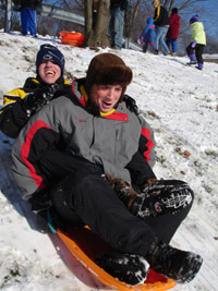 Two teenage boys sit together on a sled as it speeds down the hill