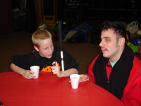 Two teenage boys sit at a table with cups of hot chocolate