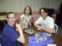 Two boys play a game of chess while a young girl looks on