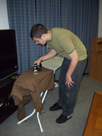 A teenage boy leans over the ironing board as he irons his dress shirt
