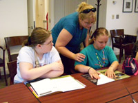 A girl, sitting at a table, reads Braille college admissions materials while another girl and a volunteer watch