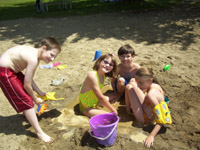 At the beach, a boy holds a shovel while the other three children sit together in the sand.