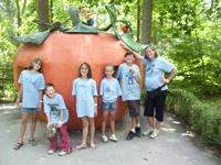A group of 5 children and an adult volunteer pose in front of a large pumpkin playhouse at Storybook Forest in Ligonier, PA