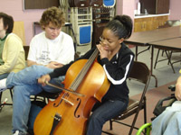 A teenage girl plays a cello while a boy watches and listens