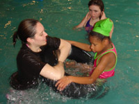 In the pool, a girl sits on the edge of an inner tube while a volunteer holds it steady