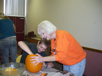 A volunteer holds a pumpkin while a teenage boy scoops out the pulp.